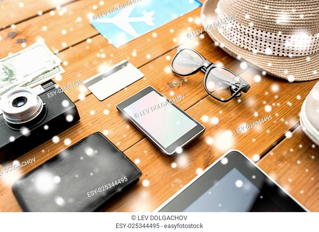 vacation, travel, tourism, technology and objects concept - close up of gadgets and traveler personal stuff