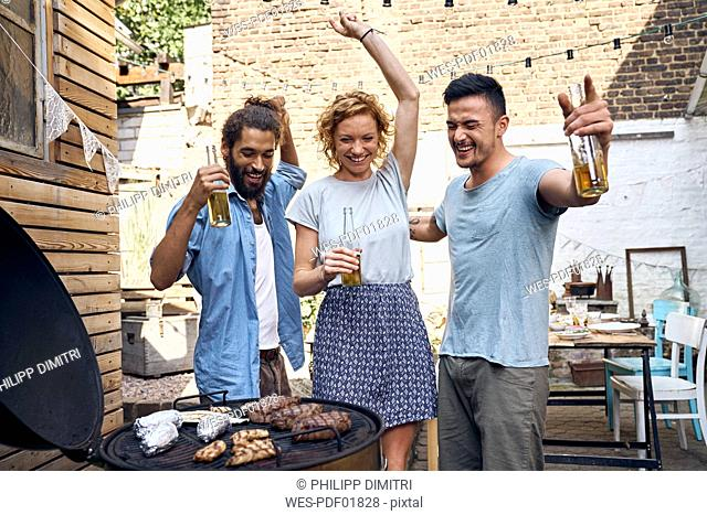Friends having a barbecue n the backyard, preparing meat on a grill