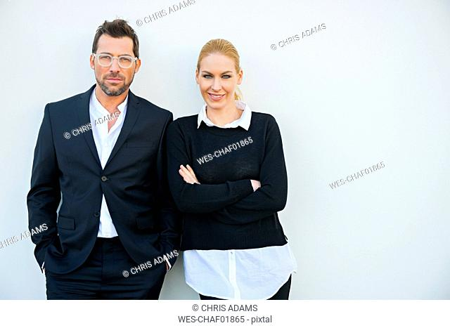 Portrait of confident businessman and woman against white wall