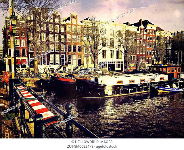Traditional Dutch houses with houseboats on the Amstel River as seen from Magere Brug (Skinny Bridge), Amsterdam, Netherlands