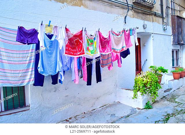 Clothes hanging to dry in a front of a house in a street, white wall. Barcelona province, Catalonia, Spain