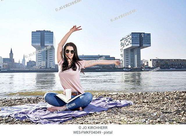 Germany, Cologne, happy young woman with book at River Rhine