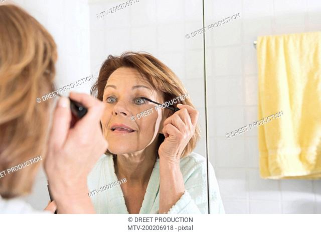 Reflection of a senior woman applying mascara, Munich, Bavaria, Germany