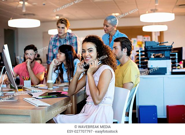 Woman with headphones working with her team in office