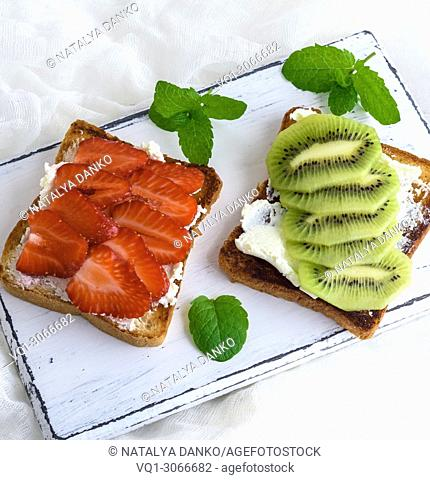 two toast with mild curd, slices of strawberry and kiwi on a white wooden board, top view