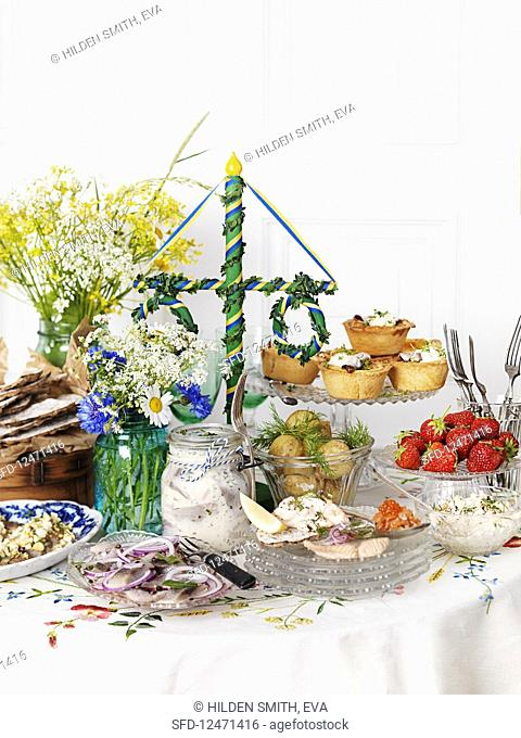 A mid-summer buffet with herring, potatoes, pies and strawberries (Sweden)
