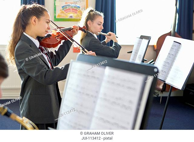 Middle school students playing violin and flute at sheet music in music class