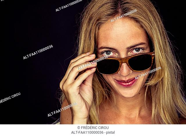 Young woman peeking over top of sunglasses, portrait