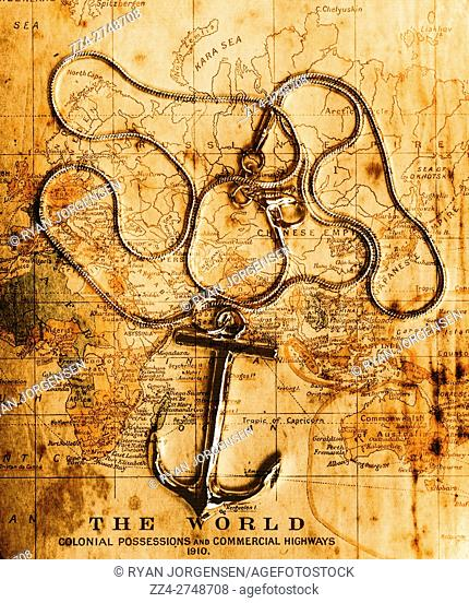Sea exploration artwork of a seamans anchor pendant on a old vintage colonial world map. Exploration in mapping