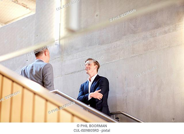 Two businessmen talking on office stairway