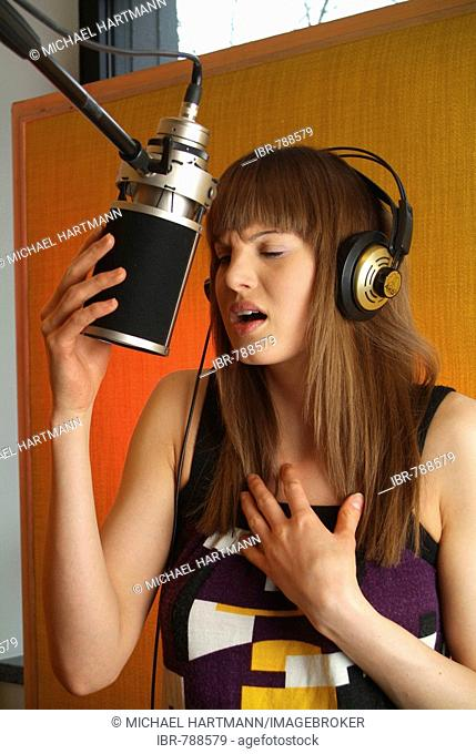 Young woman wearing headphones singing into a microphone of a recording studio