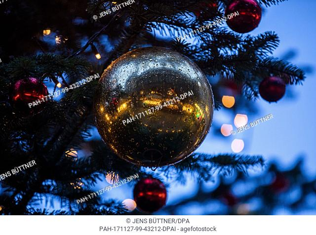 The market place is reflected in the Christmas ball covered in raindrops after the opening of the Christmas market in Luebeck, Germany, 27 November 2017