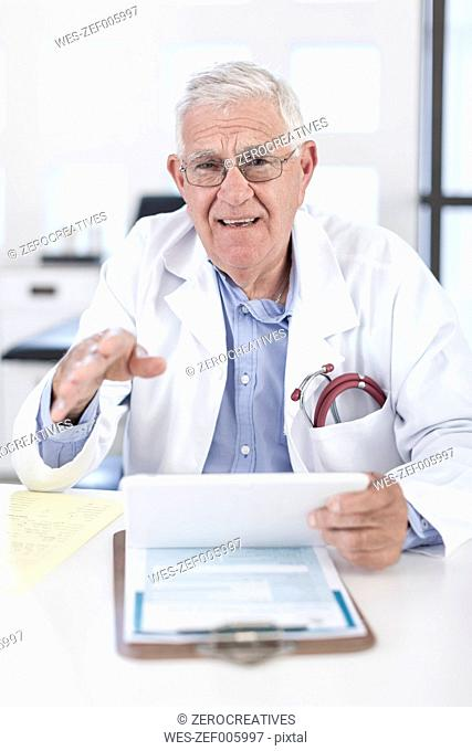 Serious senior doctor at desk discussing patient file