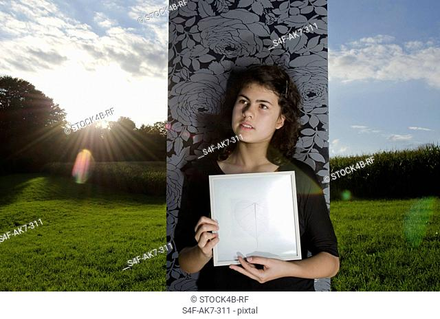 Girl holding picture frame in meadow