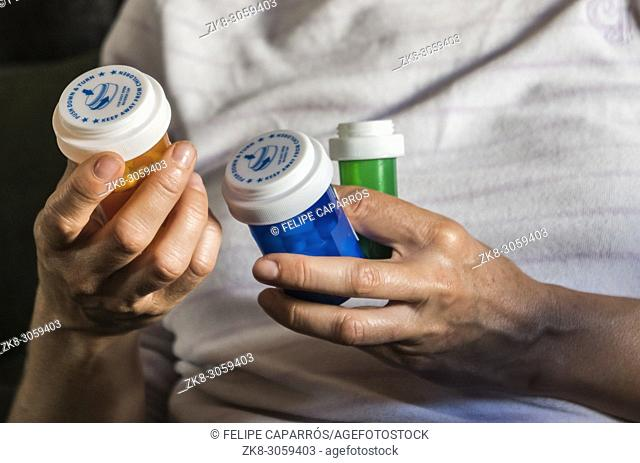 Woman examining medication treatment, several bottles in the hand, conceptual image