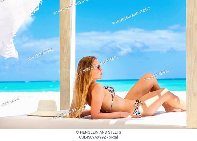 Young woman wearing bikini sunbathing on beach daybed, Dominican Republic, The Caribbean