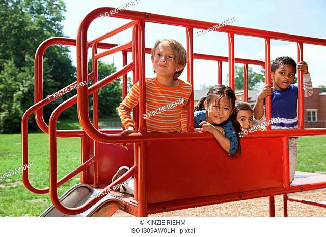 Portrait of four boys and girls on playground slide