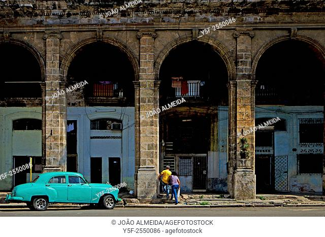 An old green car parked outside the big arcades that are só typical of Centro Habana