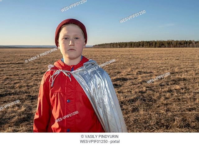 Portrait of boy dressed up as superhero in steppe landscape