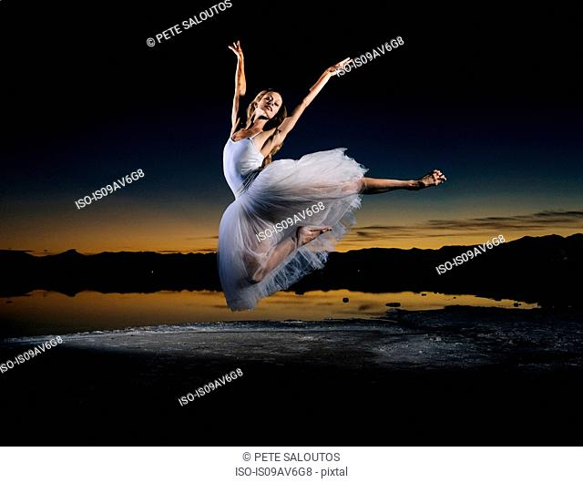 Young female ballet dancer leaping over Bonneville Salt Flats at sunset, Utah, USA