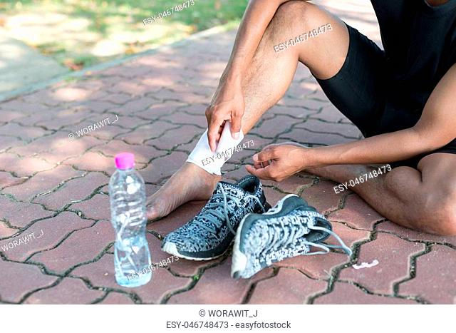 Sports injury. Asia young man runner is rewinding ankle bandage. Man with pain in ankle