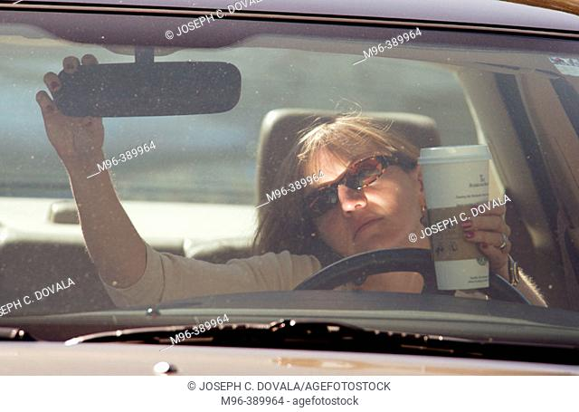 Woman driving and drinking coffee adjusts mirror