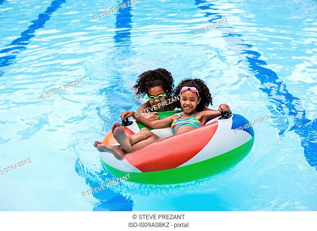 Girls in swimming pool playing with inflatable ring, looking at camera smiling