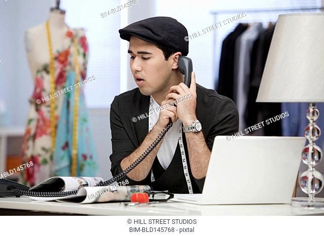 Clothing designer talking on telephone in workshop