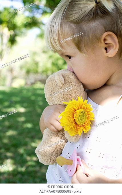 Little girl holding teddy bear, flower and pacifier