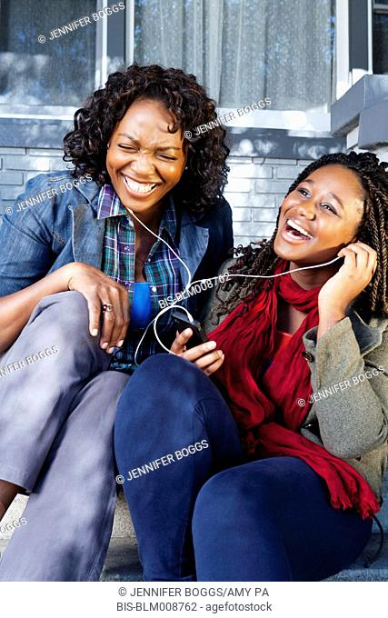 Black mother and daughter sitting on front stoop listening to music