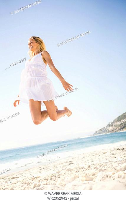 Blonde woman jumping on the beach