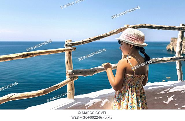 Little girl standing on balcony looking to the sea