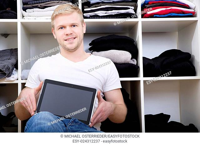 Young man sitting in front of his wardrobe with a tablet.