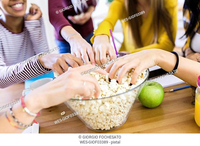 Friends taking popcorn from bowl at table at home
