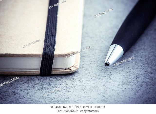 Notepad and pen lying on office desk in close up. Brown notebook and black pen. Concept of business meeting, taking notes or education