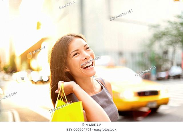 Shopper woman on Manhattan, New York City shopping having fun laughing outside in streets of New York. Fresh blissful mixed race Asian / Cauasian girl holding...