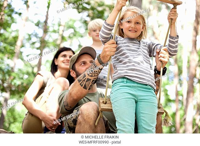 Happy family in forest with girl on swing