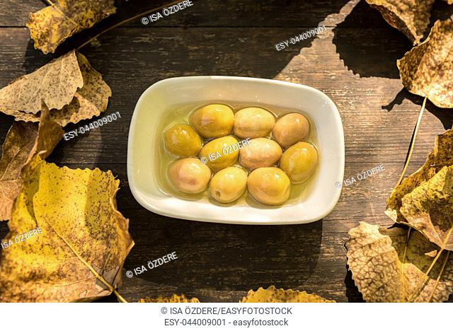 Background texture with old wooden table and top view of big green olives inside yellow autumnal leaves folded in the form of a circle
