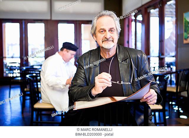 Caucasian man holding menu in restaurant