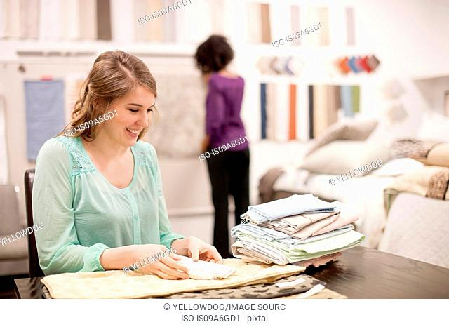 Young woman at desk with fabric samples