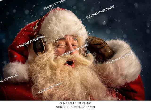 Santa Claus is listening to music in headphones wearing sunglasses. Christmas
