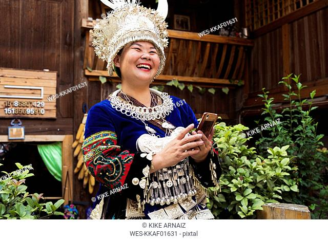 China, Guizhou, laughing Miao woman wearing traditional dress and headdress holding cell phone