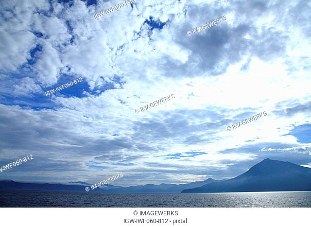 Lake Shikotsu with mount Eniwa in background against cloudy sky
