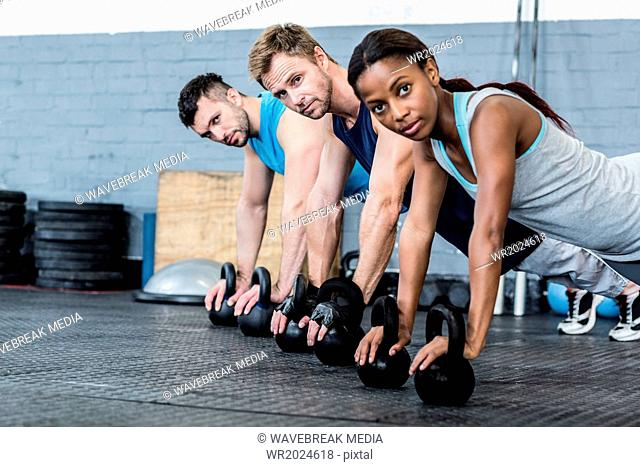 Three muscular athletes on a plank position
