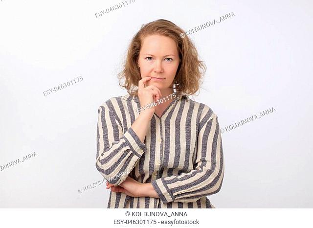 Middle aged european woman thinking and looking up, confused about an idea, would be trying to find a solution on gray background