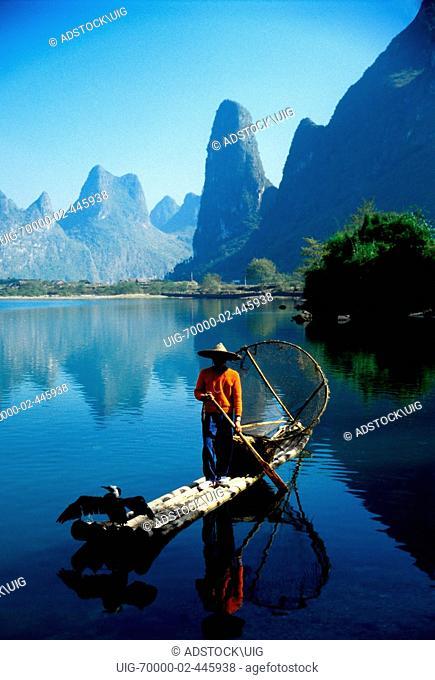 Li River, Guangxi, China: Young cormorant fisherman on bamboo raft on river near Xingping Guilin area