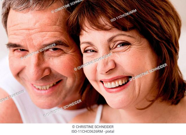 Eldery couple heads together smiling