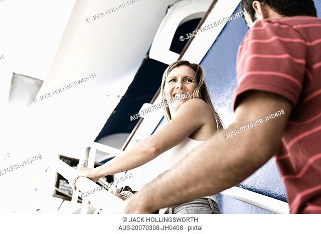 Mid adult couple walking up a staircase of a cruise ship and smiling