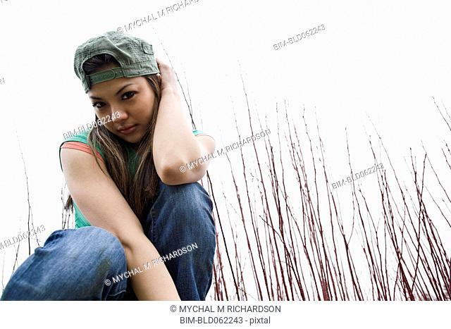 Asian woman kneeling outdoors in grass