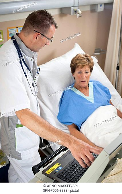 MODEL RELEASED. Nurse and patient. Nurse explaining test results to a patient